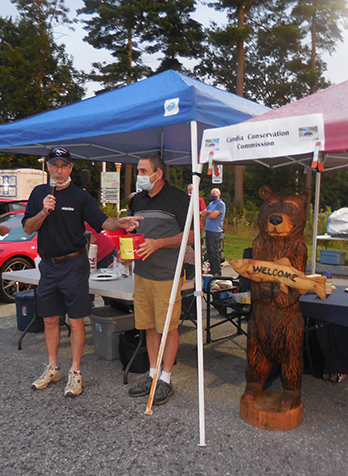 L to R: Dean Young selects the winning raffle ticket for the carved bear, Leon Austin, and the bear.